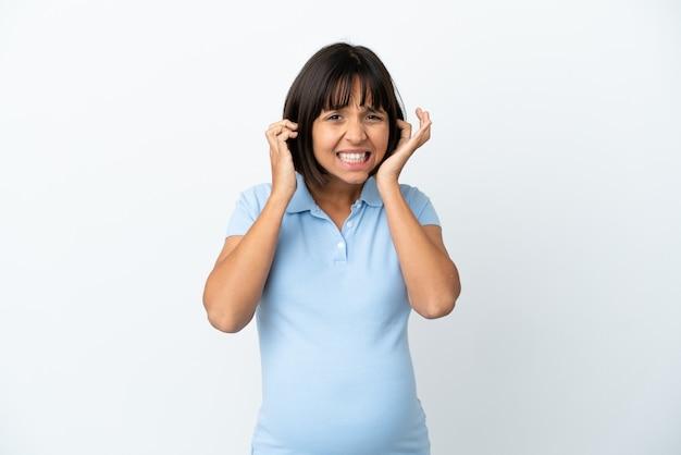 Беременная женщина на изолированном белом фоне разочарована и закрывает уши