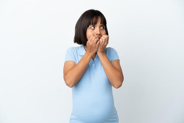 孤立した白い背景の上の妊娠中の女性は神経質で、口に手を置くのが怖い