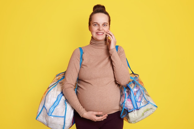 Pregnant woman packs lace baby's stuff. preparing for childbirth at home. getting ready and packing for hospital, posing isolated over yellow wall, and talks phone.