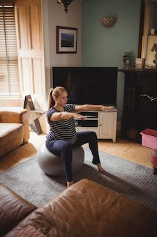 Pregnant woman performing stretching exercise on fitness ball in living room