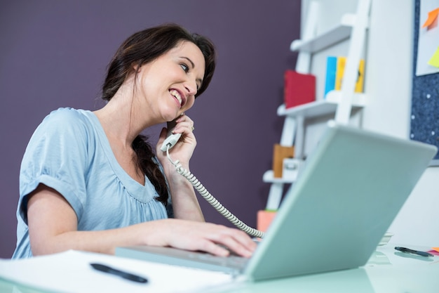 Pregnant woman on the phone at home