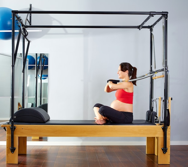 Pregnant woman pilates reformer arms exercise