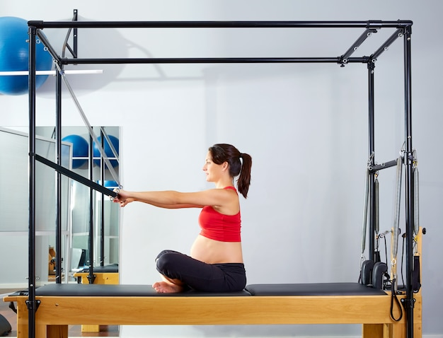 Pregnant woman pilates reformer forward push
