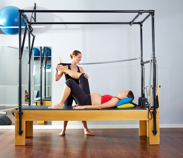 Pregnant woman pilates reformer leg spring