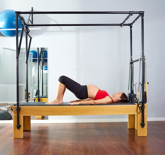 Pregnant woman pilates reformer shoulder bridge