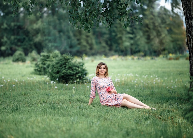 Pregnant woman in pink dress sitting on grass and touching bump