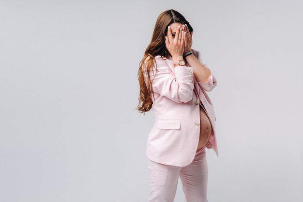 A pregnant woman in a pink suit close-up on a gray background covers her face with her hands.