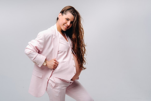 Pregnant woman in pink suit close-up on gray background.