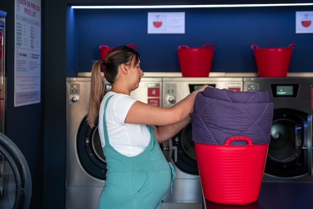 Pregnant woman placing clothes in a laundry basket in a laundromat.