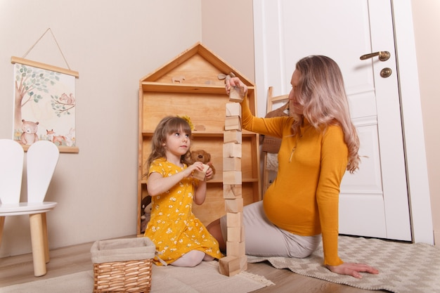 A pregnant woman plays in the nursery with her daughter. they build a tower out of wooden blocks.