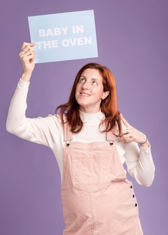 Pregnant woman pointing at paper with baby in the oven message