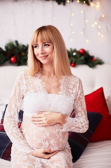 Pregnant woman portrait, new year vibes. charming blonde expecting woman