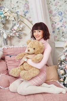 Pregnant woman posing on the bed with a teddy bear
