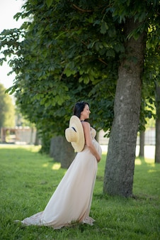 녹색 나무의 배경에 베이지 색 드레스를 입고 포즈를 취하는 임신 한 여자.