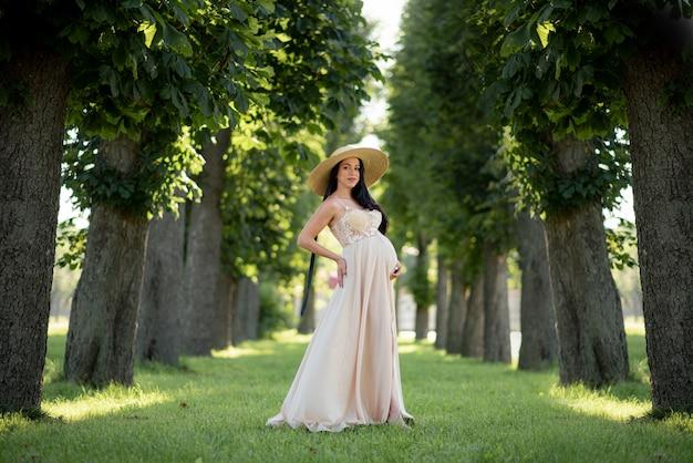 妊娠中の女性が緑の木々にベージュのドレスでポーズします。