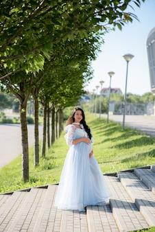 妊娠中の女性が緑の木々の青いドレスでポーズします。