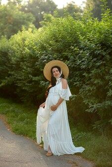 妊娠中の女性が自然に白いドレスでポーズします。