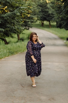 Беременная женщина позирует в парке