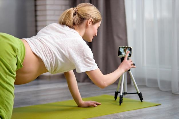 Беременная женщина занимается йогой дома со смартфоном, будущая мать делает пренатальный видеоурок