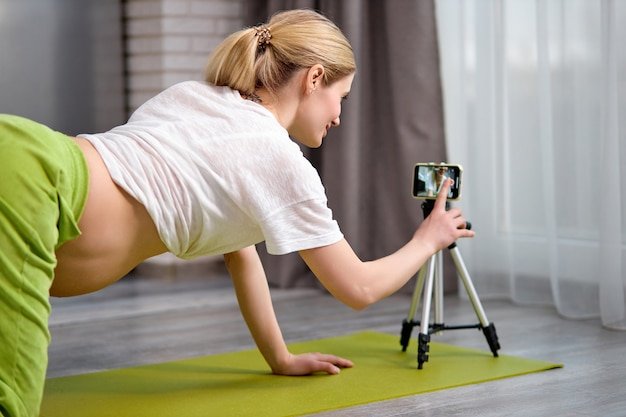 Pregnant woman practicing yoga at home with smartphone expectant mother doing prenatal video training class
