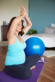 Беременная женщина занимается йогой каждый день