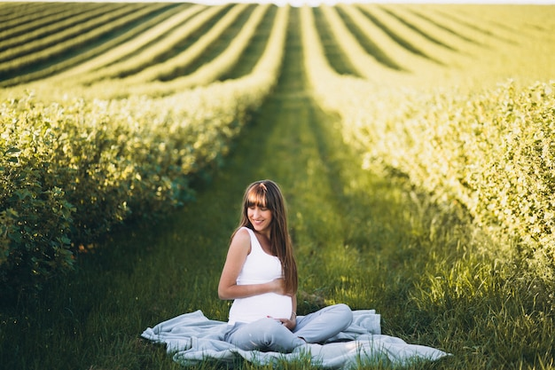 Pregnant woman practising yoga in field