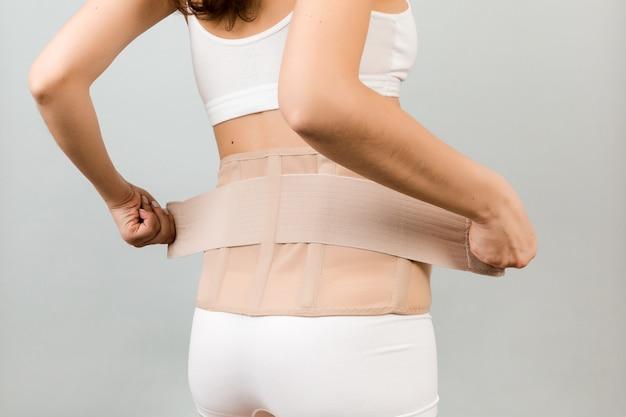 Беременная женщина надевает поддерживающую повязку