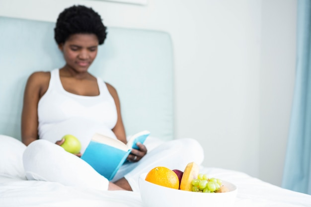 Pregnant woman reading a book lying on her bed