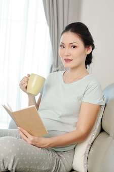 Беременная женщина, читающая