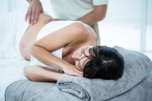 Pregnant woman receiving a back massage from masseur at the health spa