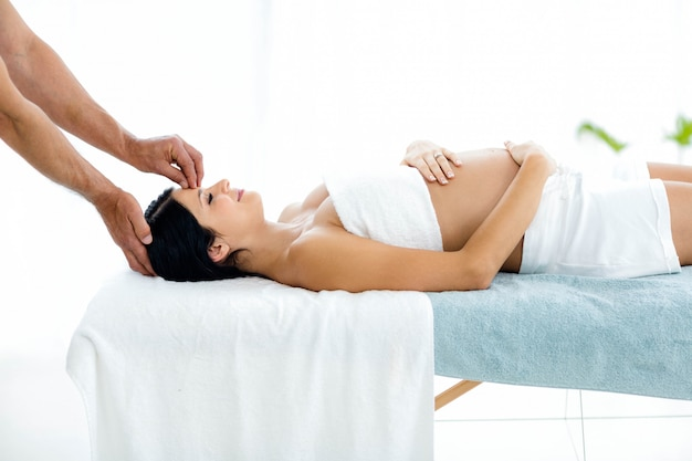Pregnant woman receiving a head massage from masseur at home