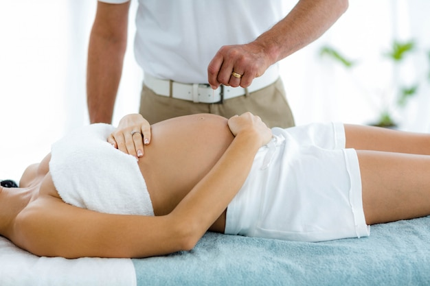 Pregnant woman receiving a spa treatment from masseur at home