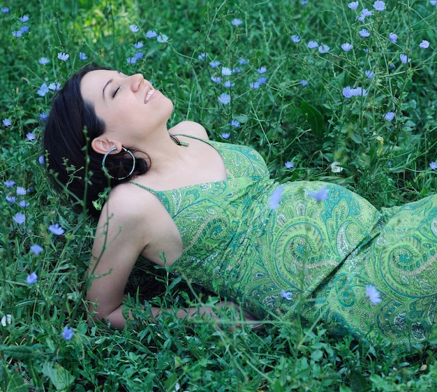 Pregnant woman relaxing on grass.