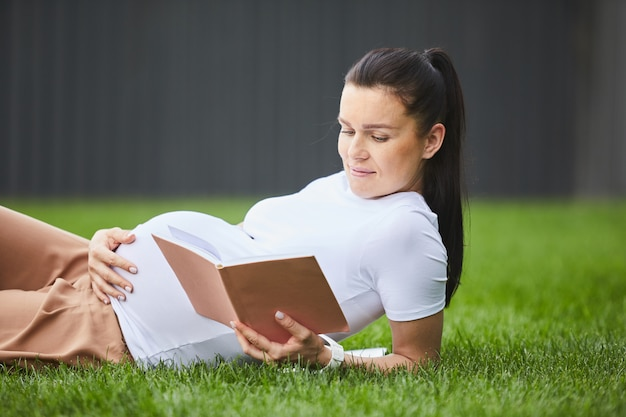 Pregnant woman relaxing with book
