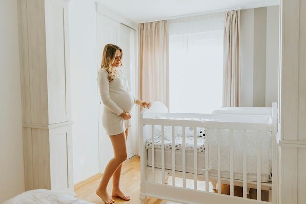 Беременная женщина, создающая детскую кроватку