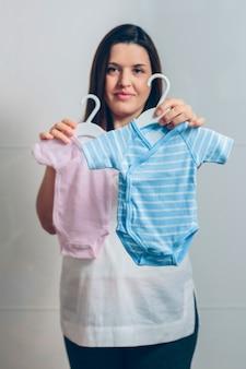 屋内で赤ちゃんのボディスーツを見せている妊婦。前景の青いボディスーツに選択的に焦点を当てる