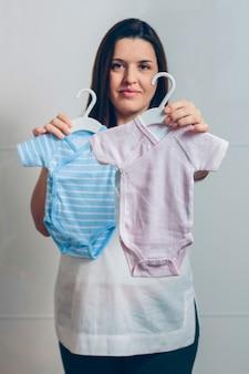 屋内で赤ちゃんのボディスーツを見せている妊婦。フォアグラウンドでピンクのボディスーツに選択的な焦点