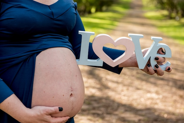 妊娠中の女性は腹を示し、愛を書いたサインを保持しています。