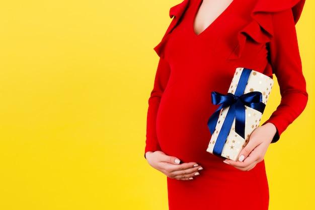 임신 한여자가 그녀의 배꼽을 보여주는
