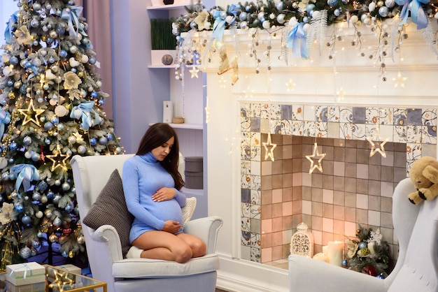 Pregnant woman sits in an armchair by the window next to christmas tree. she looks thoughtfully at her belly.