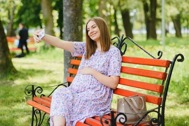 Pregnant woman sits on bench in the park and using phone