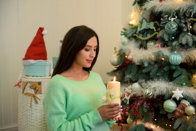 Pregnant woman sits near christmas tree with a candle in her hands.
