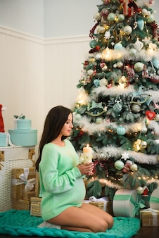 Pregnant woman sits  near christmas tree with a candle in her hands
