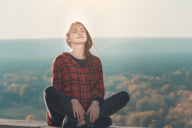 Беременная женщина сидит на холме с закрытыми глазами. медитация. осенний лес на заднем плане