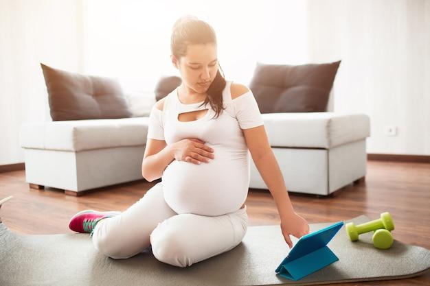 Беременная женщина сидит на коврике для йоги и использует мобильное приложение на планшете для занятий спортом во время беременности.