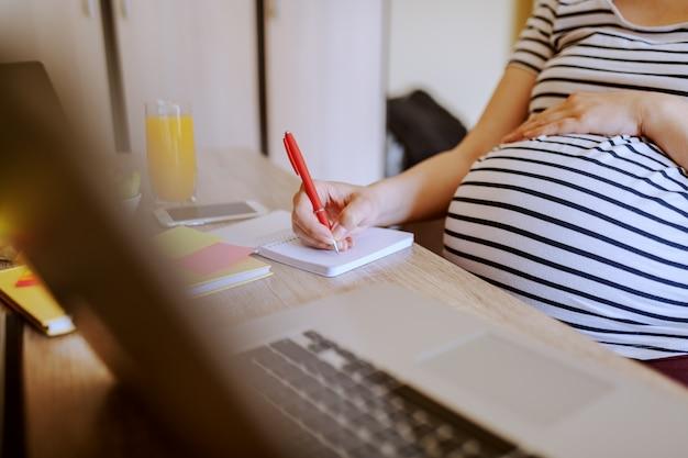 妊娠中の女性がテーブルに座って、ノートに書きます。机の上で健康的な朝食とラップトップ。妊婦のコンセプト。