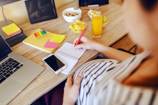 妊娠中の女性がテーブルに座って、ノートに書きます。机の上で健康的な朝食、ラップトップ、スマートフォン。妊婦のコンセプト。