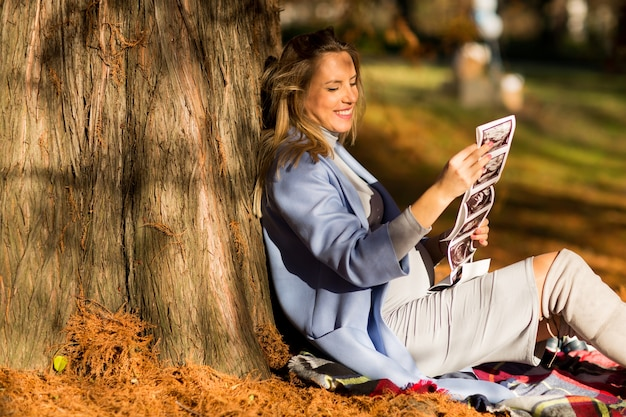 Pregnant woman sitting in autumn park