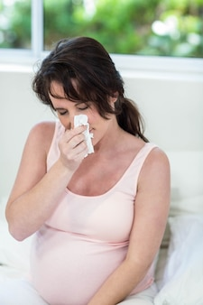 Pregnant woman sitting on bed sneezing