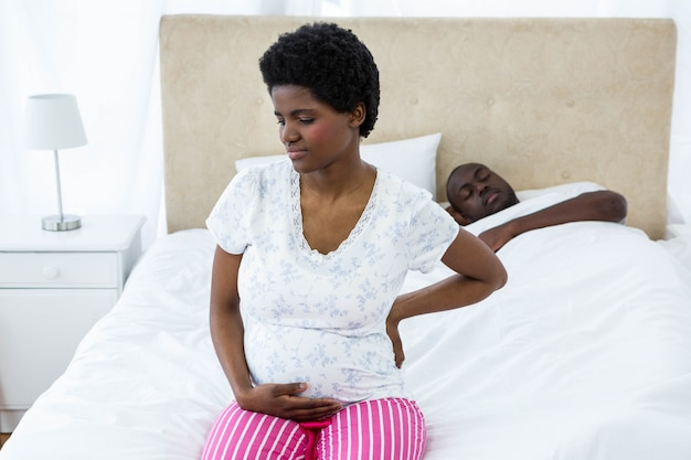 Pregnant woman sitting on bed while husband sleeping behind